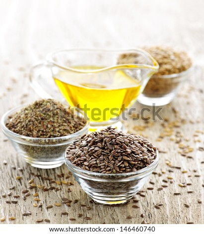 Bowls of whole and ground flax seed with linseed oil - stock photo