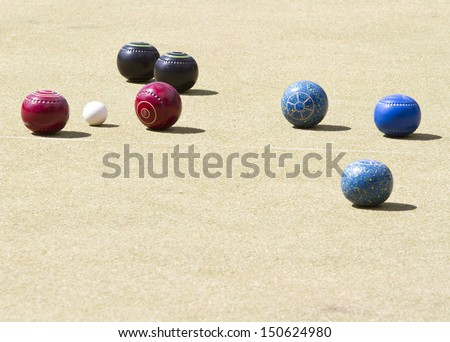 Bowls or lawn bowls is a sport played on outdoor lawn which is natural grass or artificial turf.  The objective of the game is to roll biased balls to stop close to a smaller ball  jack or kitty. - stock photo