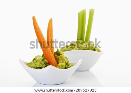 Bowls with avocado cream, taco chips, celery and carrots