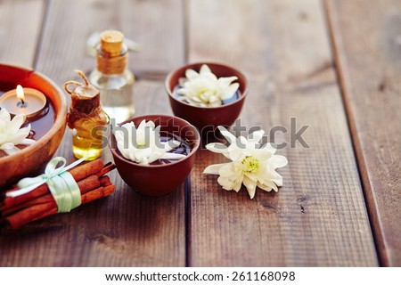 Bowls with flowers, bunch of cinnamon for aromatic oil - stock photo