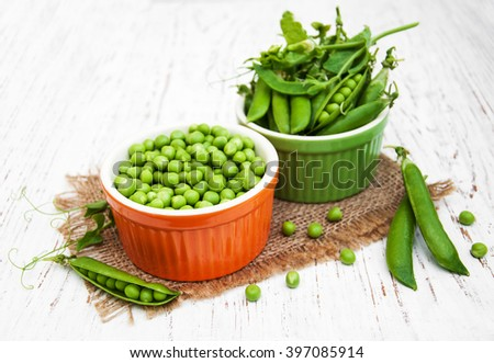 Bowls with fresh peas on a wooden background - stock photo