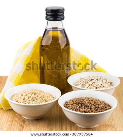 Bowls with oats, buckwheat, brown rice and bottle oil isolated on white background - stock photo