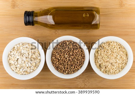 Bowls with oats, buckwheat, brown rice and bottle oil on wooden table, top view - stock photo