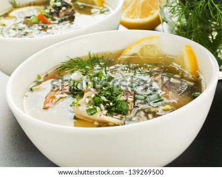 Bowls with soup with sturgeon and vegetables. Shallow dof. - stock photo