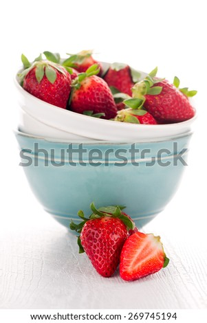 Bowls with strawberries on white table background. - stock photo