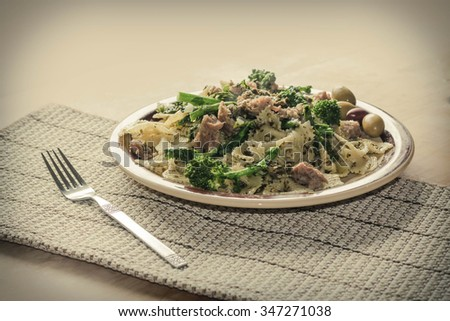 Bowtie pesto pasta with ground sausage and broccoli rabe garnished with fancy olives - stock photo