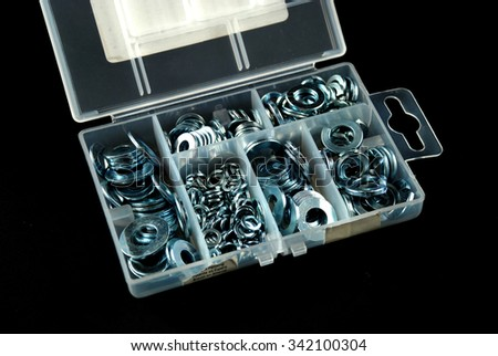 box containing several nuts and washers of different sizes - stock photo
