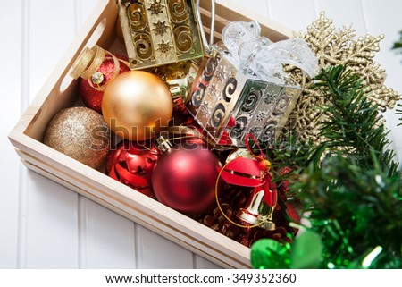 Box filled with Christmas decorations on white background - stock photo