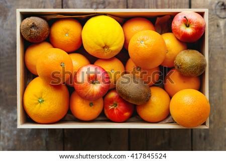 Box full of fresh fruits. Fruit harvest - apples, oranges, lemon, kiwi. Rustic wooden table. - stock photo