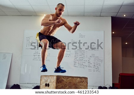 Box jump exercise - young man doing functional workout at the gym