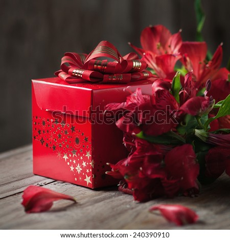 box of chocolate truffles with red flowers on wooden background, square image