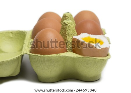 Box of Eggs with one broken boiled egg isolated on white background - stock photo