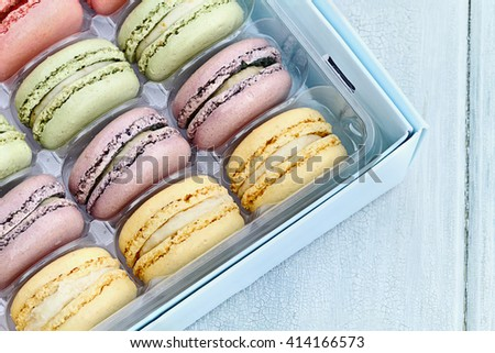 Box of fresh pastel colored macarons shot from overhead.