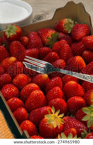 Box of freshly picked strawberries. Cultivated worldwide and consumed in large quantities, either fresh or in prepared foods, preserves, fruit juice, pies, ice creams, milkshakes, and chocolates - stock photo
