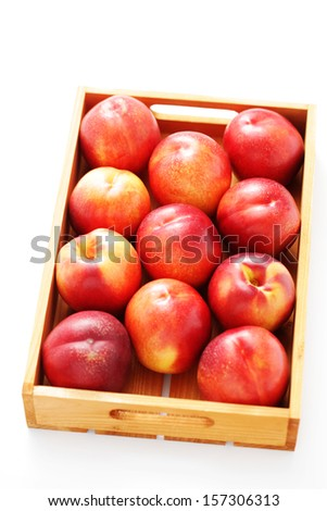 box of nectarines on white background - fruits and vegetables