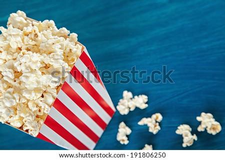 Box of popcorn on blue background - stock photo