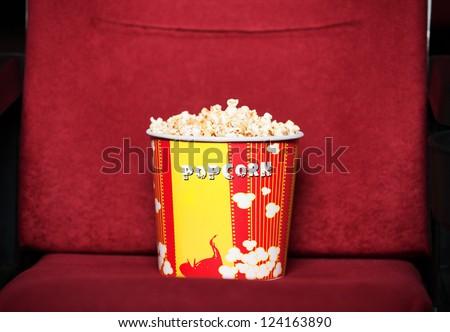 Box of popcorn on cinema chair - stock photo
