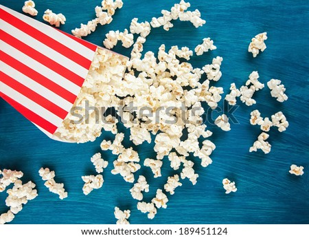 Box of popcorn spilled on blue background. - stock photo