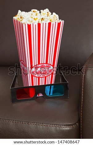 Box of Popcorn with 3D TV glasses on a brown leather home cinema chair.