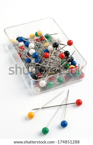 Box of sewing or push pins with round plastic heads studio isolated - stock photo