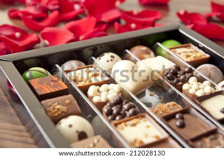 Box of tasty chocolates among rose petals - a romantic valentine gift - stock photo
