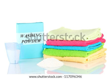Box of washing powder with blue measuring cup and towels, isolated on white