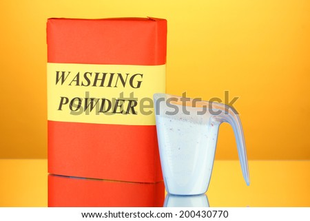 Box of washing powder with blue measuring cup, on orange background close-up