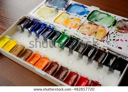 box of watercolors on wooden desk