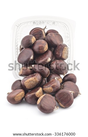 Box or punnet and spilled fresh organic chesnuts isolated on white background - stock photo