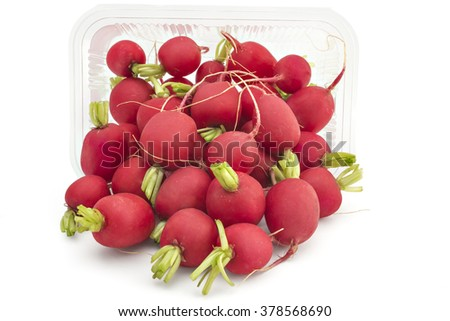 Box or punnet and spilled raw organic small garden radishes isolated on white background - stock photo