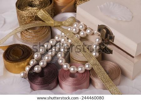Box, pearls and ribbons - stock photo
