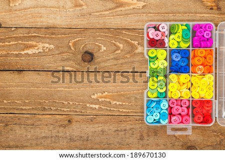 Box with colorful sewing buttons on a wooden background with copy space.  - stock photo