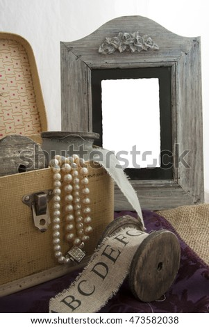 Box with old items spool in front and empty picture frame
