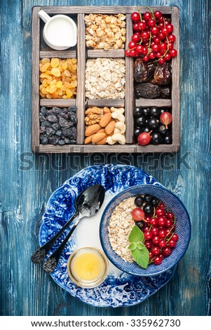 Box with products for healthy breakfast. Muesli, oatmeal, dried fruit, fresh berries  and nuts. - stock photo
