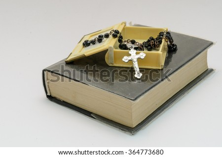 box with rosary on small black book on white background - stock photo