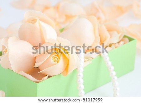 Box with rose petals and pearls - stock photo