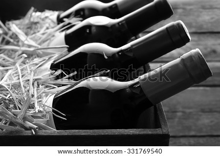 Box with straw and wine bottles,  black and white retro stylization - stock photo