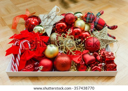 Box with toys to decorate Christmas (new year) pine tree. Decorative toys in classical colors: red and golden yellow. Selective focus on the center of the image. - stock photo