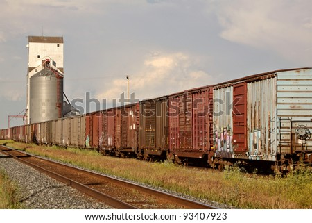 Boxcars parked on siding near grain elevator - stock photo