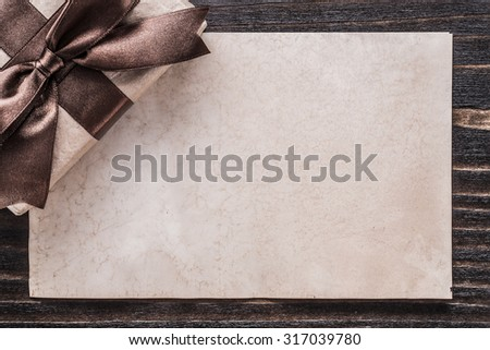 Boxed gift with tied bow paper on vintage wooden board. - stock photo