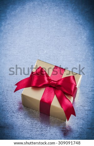 Boxed golden present with red ribbon on metallic background. - stock photo