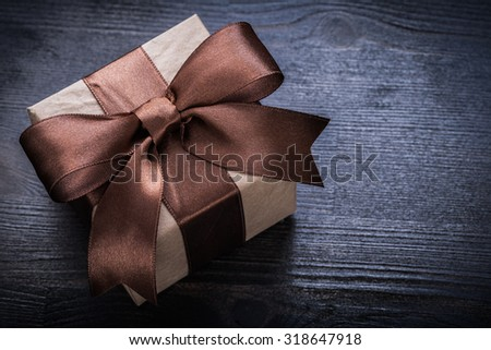 Boxed present tied bow on wood board close up view.
