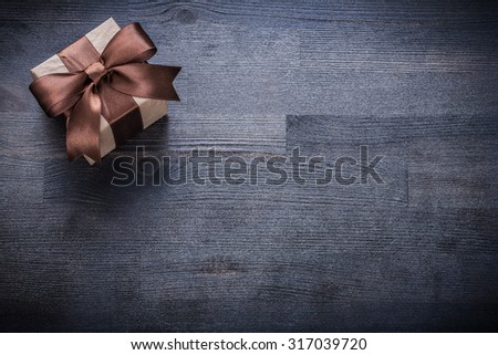 Boxed present with brown bow on vintage wooden board copyspace. - stock photo