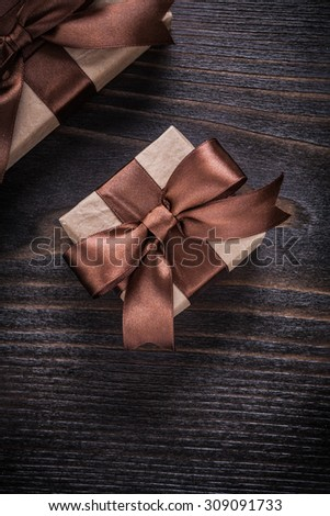 Boxed presents with brown ribbons on vintage wood board.