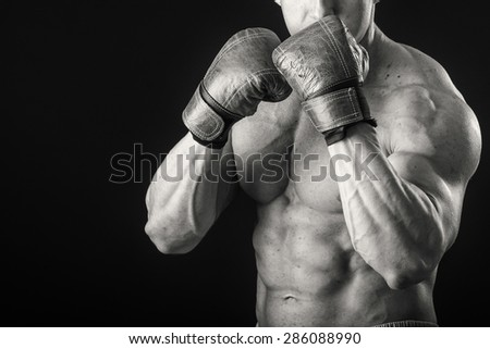 Boxer. Black and white stock photography. Man with boxing gloves on a black background.