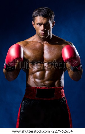 Boxer Boxing staring showing strength. Young man looking aggressive with boxing gloves. Caucasian male model isolated on dark background. - stock photo