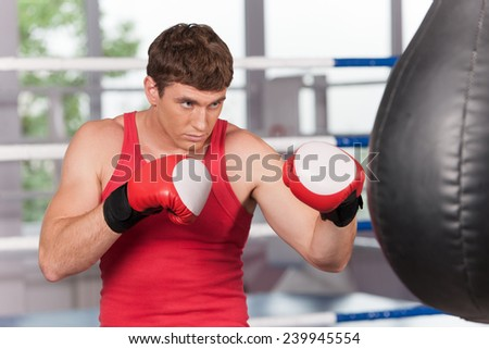 Boxer doing some training on punching bag at gym. Young caucasian Boxer training with punching bag in gym  - stock photo