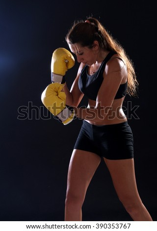 Boxer. Fitness woman wearing yellow boxing gloves over black background