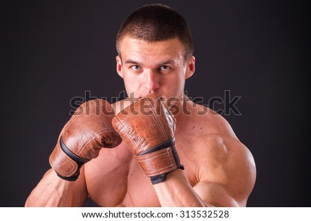 Boxer in boxing gloves. Boxer shows his body and technology effort on a dark background. Concentration and stress. Sport Training. - stock photo