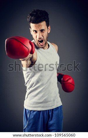 boxer is giving a straight punch while screaming - stock photo